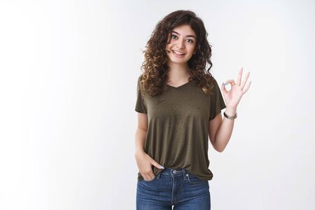 Portrait cute armenian curly-haired woman in olive t-shirt show okay gesture thinking outfit not bad agree say ok, smiling give approval confirm everything goes as planned, standing white background