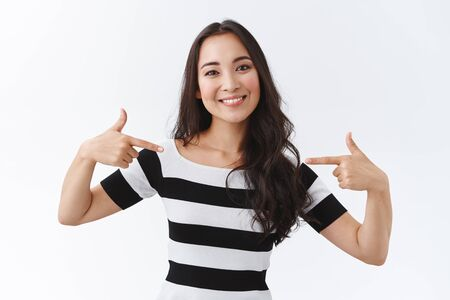 Carefree, outgoing good-looking asian woman in striped t-shirt pointing herself as propose own candidature, talking personal achievements, bragging or boastful talking, white background