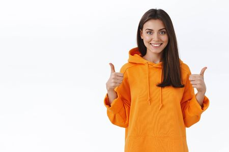 Happy satisfied good-looking female student in orange hoodie recommend online course, praise great job, show thumbs-up and smiling delighted, leave positive review, white background