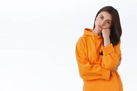 Thoughtful and bored gorgeous caucasian brunette female in orange hoodie, lean on fist and pouting, squinting suspicious at camera, thinking how spend leisure, stand white background