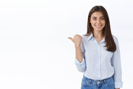 Girl suggest turn your attention to this promo banner, give advice where find help and provide service. Pleasant professional brunette female entrepreneur pointing left with thumb smiling friendly