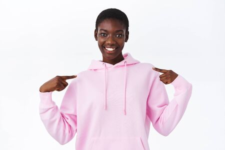 Cool young african-american girl with short hair pointing at herself and smiling, boastful talking own achievement, introduce, want to volunteer, applying for job position, white background