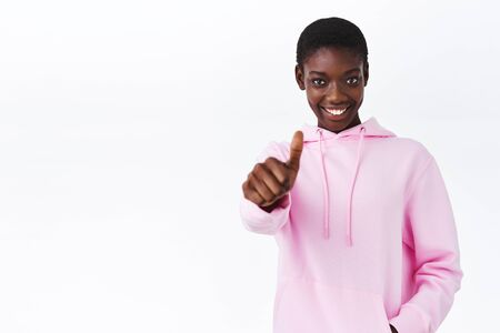 Go for it, sounds cool. Happy and satisfied african-american girl with short hair in pink hoodie, extend hand with thumb-up and smiling, encourage, approve and like product, recommend it