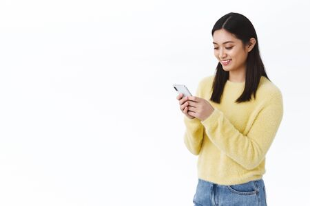 Happy cute asian girl using mobile phone and smiling. Female student sending funny meme via social media messanger, chat with friends or team members, video-call on smartphone, white background