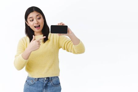 Excited happy kawaii asian girl pointing and showing funny video or shot on smartphone display, look amused, passionately talking about new funny game or application, white background