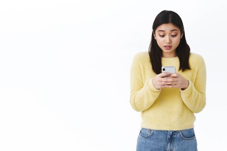 Girl typing message in hurry. Cute asian woman using smartphone, hold mobile phone and looking at screen intrigued, playing interesting new game download from store, standing white background