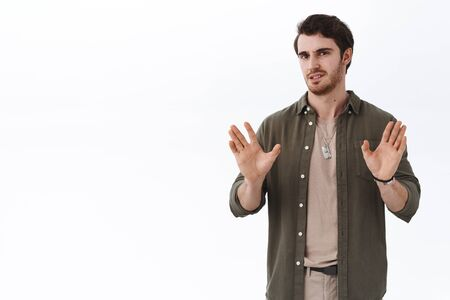 Quit this bullshit. Serious-looking busy handsome guy showing stop, enough or dont gesture with hands raised near chest, grimacing disappointed, uninterested in seller offer, white background