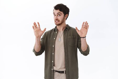 Guy trying avoid conflicts, lift hands up to calm down person. Reluctant and nervous handsome man got in trouble solve argument with people, shaking arms to apologize and go away, white background