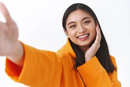 Close-up portrait tender pretty asian girl in orange hoodie, touching pretty clean face and smiling, taking selfie on mobile phone, stretch hand to hold camera, make cute expression, white background