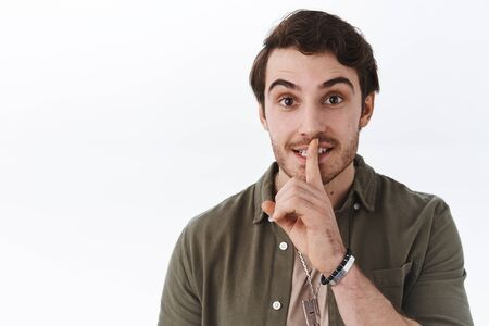 Cute bearded guy in casual outfit asking keep secret safe, shush be quiet with index finger pressed to lip, smiling happy and friendly, please stay silent gesture, standing white background