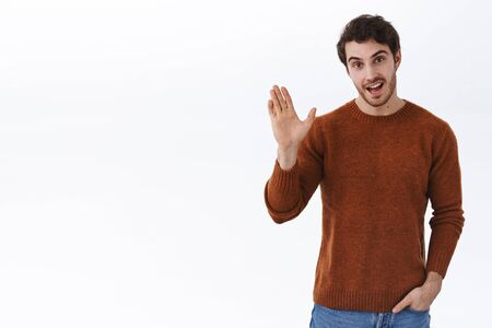 Hi there. Handsome caucasian 25s guy in sweatshirt, hold hand in pocket and casually informal greet person, smiling and waving raised hand in hello gesture, welcome, introduce himself