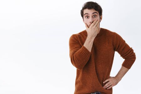 Impressed young man hear fresh gossip cant believe its true, staring popped eyes camera, cover mouth astonished, startled with amazing news, standing thrilled and speechless white background