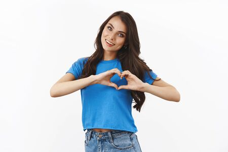 Tender, feminine brunette female in basian blue t-shirt, tilt head cute, smiling and showing heart gesture, express sympathy or love, saying I like you, standing white background joyful