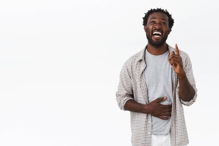 Guy recalled funny joke, raising one finger and looking up, holding belly as laughing out loud, smiling and chuckling from hilarious moment, standing white background carefree and upbeat