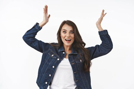 Surprised girl hearing happy news, raising hands up relieved and joyful, rejoicing over winning prize, triumphing celebrating victory, become champion, congratulating with win, white background 스톡 콘텐츠