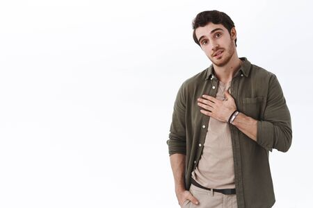 Handsome caucasian guy being honest, telling truth, holding hand on chest to express his sincere feeling, looking camera, thanking for help, grateful or pleased with something, white background