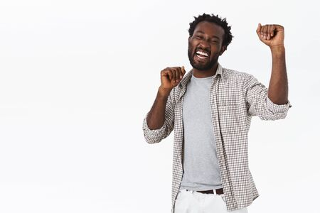 Happy, enthusiastic good-looking african-american bearded man do lucky dance, celebrating success, raising hands up in hooray, achieve victory or approval, winning lottery, stand white background