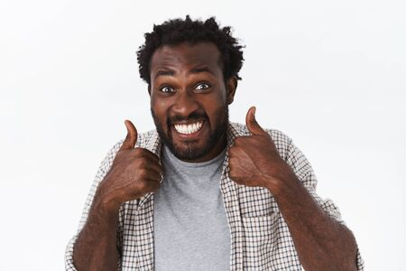 Impressed, excited happy, funny african-american bearded guy totally agrees with awesome choice or plan, show thumbs-up judging amazing event, like stunning performance, smiling satisfied Stock Photo