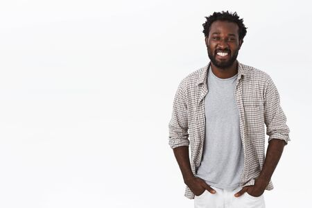 Outgoing, sociable happy african-american male with beard, afro haircut, hold hands in pockets and smiling broadly, looking carefree and enthusiastic, talking with friend, white background