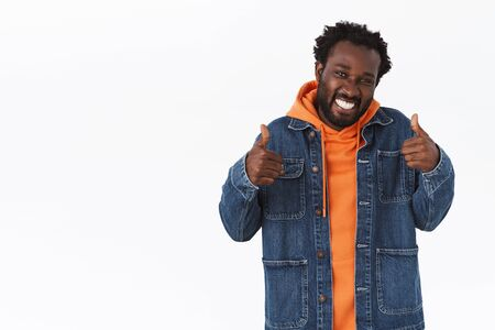 Supportive handsome african-american boyfriend showing thumbs-up in like or approval, smiling pleased, rooting for you or give his positive reply, feedback, agree with good choice, white background