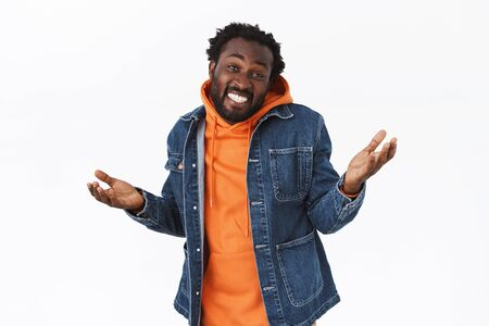 Carefree, relaxed and unbothered stylish african-american man in denim jacket, orange hoodie, raising hands sideways clueless or unaware, smiling careless, not worrying, standing calm and happy 스톡 콘텐츠