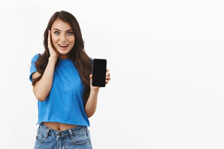 Happy, touched and impressed young woman found excellent app courses, video tutorial, showing on smartphone screen, touching face amused smiling, happy and pleased over white background