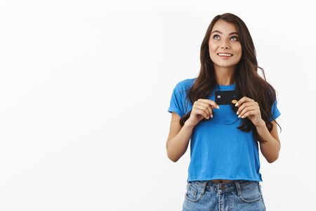 Dreamy adorable young woman in basic blue t-shirt, dreamy looking up, imaging what she will buy in store, holding credit card like treasure, standing white background, smiling Stock Photo