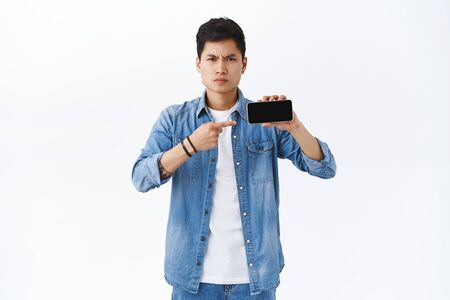 Technology, online lifestyle concept. Portrait of angry disappointed young asian man found his drunk photos on friends internet profile, pointing at mobile phone with annoyed bothered expression