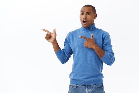 Portrait of shocked, speechless african-american male in turtleneck, pointing fingers left, drop jaw, gasping concerned and astonished, startled over shook news, white background Stockfoto