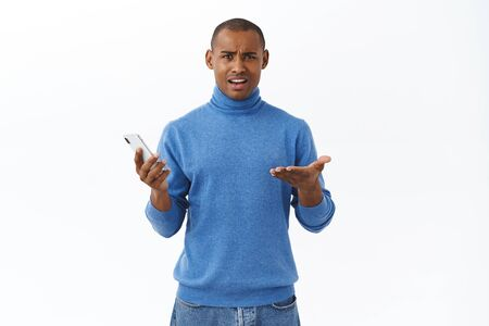 Technology, online lifestyle concept. Portrait of displeased young african-american man shrugging in dismay, being disappointed, holding mobile phone, read strange frustrating news internet Reklamní fotografie