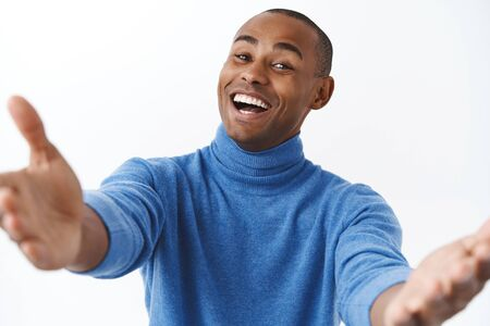 Close-up portrait of friendly lovely african american boyfriend reaching his hands toc amera, want to cuddle someone, embrace dearest person, welcoming guest, standing white background
