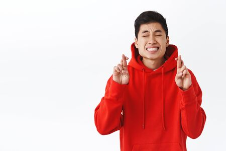 Portrait of pleading young nervous asian man in red hoodie, close eyes and clench teeth intense as dreaming, cross fingers good luck, praying want dream come true, making wish, white background Reklamní fotografie