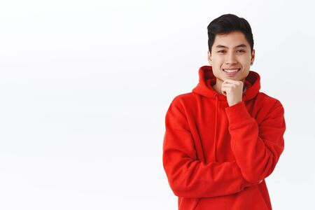 Portrait of curious good-looking asian man spot interesting thing, look with amusement and approval, smiling touch chin, picking something, making decision, standing white background