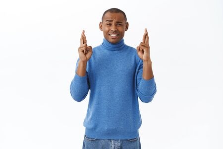 Portrait of hopeful young african-american man cross fingers good luck, frowning and squinting worried, awaiting important results, praying for dream come true, making wish over white background