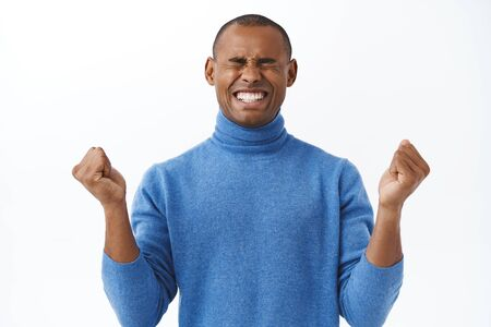 Portrait of encouraged young african american man boosting confidence, fist pump, close eyes and smiling, motivating himself stay positive, move on, facing depression or stress, white background