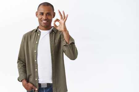 Portrait of confident african-american man show okay, ok sign and smiling, nod in approval, give positive feedback, approve and agree, white background Stockfoto