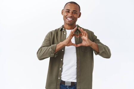 Portrait of happy handsome romantic man in casual clothes, sharing his love and happiness with family, show heart gesture and smiling sincere, confess sympathy, standing white background