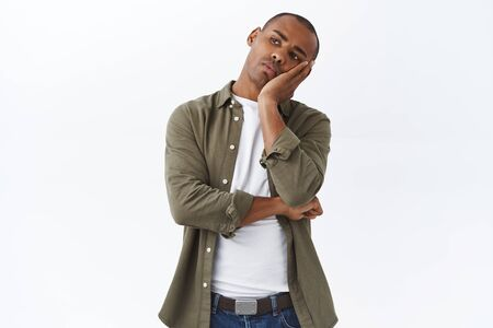 Portrait of bored african-american man, lean face on palm, staring with indifferent and boredom left, watching tv at home during quarantine, dont know what do, feel sad, white background Stock Photo