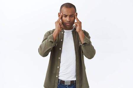 Portrait of focused, african american man feel stress, trying calm down and be patient, massaging temples, close eyes, suffer headache or migraine, need painkillers medicine, white background Imagens