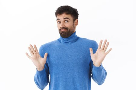 Portrait of reluctant and uninvolved bearded guy shaking hands in denial, rejecting and smirk, know nothing, being clueless about topic, have no idea, stand white background Stock Photo