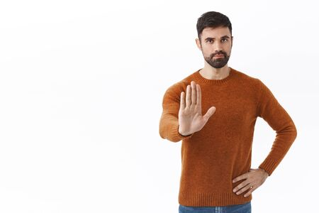 Portrait of handsome confident bearded man, stretching hand in prohibition, disapprove behaviour, forbid action, dont come outside during quarantine, white background
