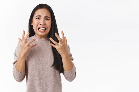 Freak-out outraged and overreacting east-asian girl in panic, gesturing betrayed and anger, raging in fury, having mental breakdown, lost someone important, standing upset white background