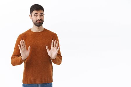 Skeptical and unimpressed handsome male entrepreneur, guy show stop, shaking hands in rejection and smirk, sorry dont want it, refuse participate in strange event, white background Stock Photo