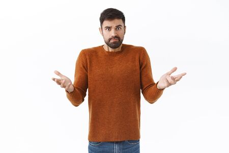 Portrait of frustrated and shocked handsome bearded man, staring confused camera, raise hands in dismay, cant understand what happened, dont know what do, stand indecisive white background.