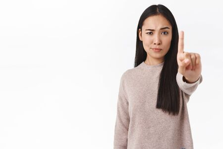 Serious and confident asian female prohibit and warn friend, demand stop, stretch finger forward in taboo, rejection gesture, smirk skeptical and displeased, don't like what happening