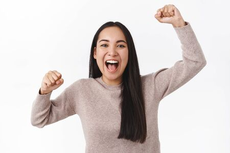 Cheerful excited asian girl rooting for football team, raising hands up, fist pump and smiling, shout from adoration and thrill, devoted fan want win. Woman triumphing as become champion competition