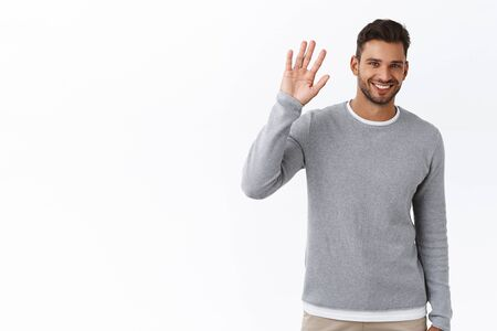 Friendly modest handsome bearded man in grey sweater saying hi with hesitation lifting one palm, waving hand in hello, greeting gesture, smiling cute, standing white background, meet new people