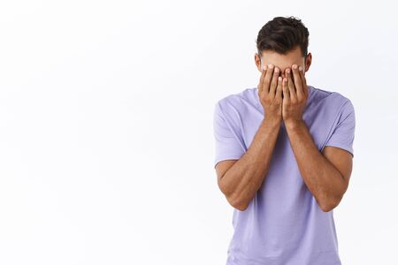 Reckless distressed, depressed young millennial guy in purple t-shirt, tired of problems, dont know how solve situation, cover face with hands, facepalm from fatigue and annoyance, white background Standard-Bild