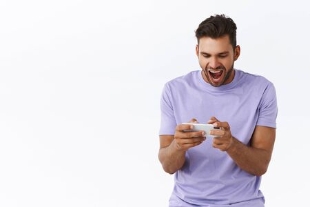 Cheerful, excited good-looking hispanic bearded guy in purple t-shirt, looking astonished and thrilled, playing awesome new smartphone game, yelling and smiling pleased, winning, white background