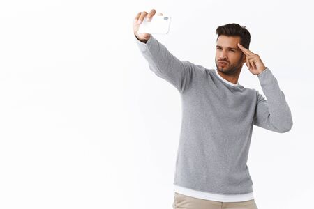 Handsome cheeky stylish young bearded man send positive vibes to followers as record live stream using mobile app, man making sexy face and hold hand near forehead like pilot as taking selfie 写真素材